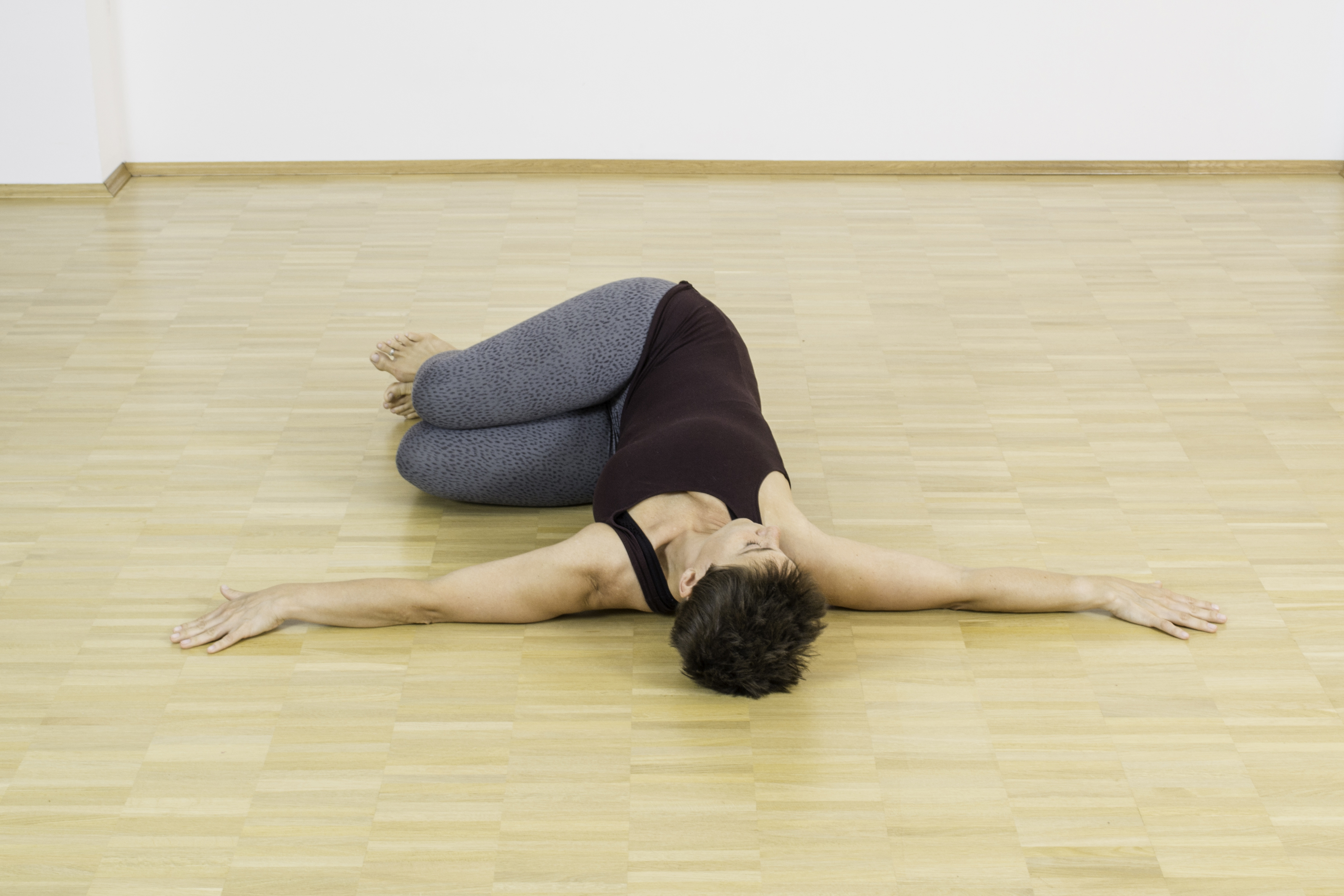 Das Krokodil ist eine ganz wunderbare Asana im Yoga, denn sie bietet dem unteren Rücken eine wundervolle Entlastung. Komme hierfür zunächst in Rückenlage und breite Deine Arme auf Schulterhöhe zu den Seiten aus. Winkel dann Deine Beine an und mache mit Deiner Hüfte einen kleinen Hosper nach rechts. Anschließend lässt Du Deine beiden Beine achtsam zur linken Seite sinken, Dein Blick geht zur rechten Seite. Achte darauf, dass Deine beiden Schultern auf dem Boden bleiben. Lasse mit jeder Ausatmung mehr los. Halte diese Asana etwa 8 tiefe Atmezüge. Drehe Dich dann einatmen zur Mitte zurück, wechsele die Seiten und lasse ausatmend die Beine zur rechten Seite fallen, Dein Blick geht nach links.