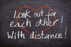 """Bild mit der Schrift: """"Look out for each other! With distance"""". Im Hintergrund ist ein rotes Herz zu sehen."""