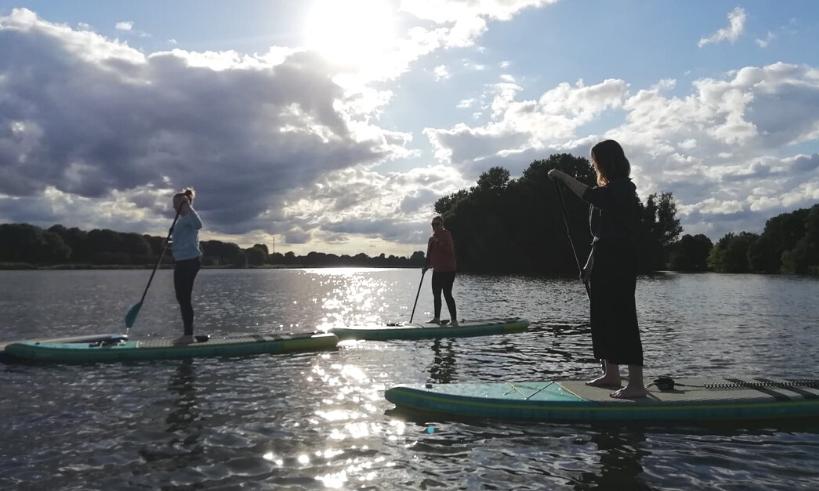 Drei Frauen stehen auf einem Stand-Up-Paddel auf einem See in der Sonne