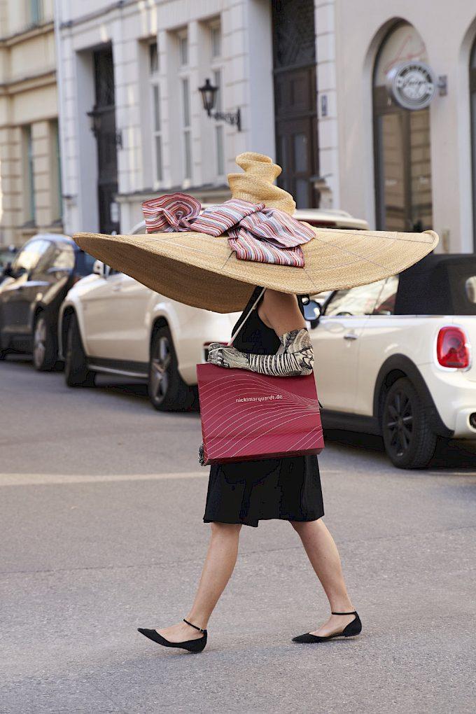 Eine Frau, die über eine Straße geht und einen überdimensionalen Hut trägt.