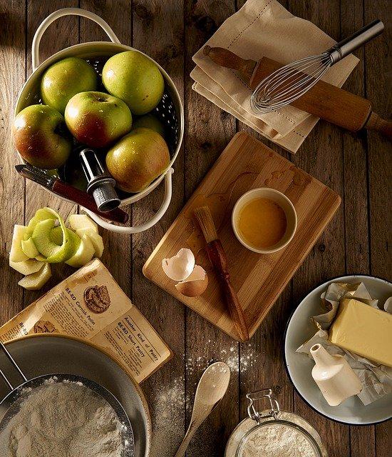 Holztisch mit verschiedenen Küchenutensilien und Lebensmitteln wie zum Beispiel Äpfel, Butter, Eier, Mehl, Schneebesen und Kochlöffel.