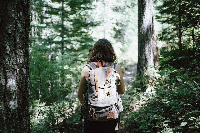 Frau trägt einen großen Rucksack und geht im Wald spazieren.