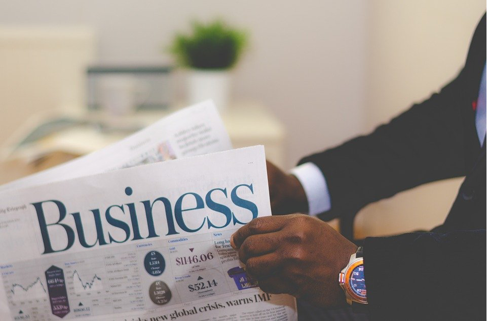 Ein Mann liest eine Zeitung mit dem Titel Business