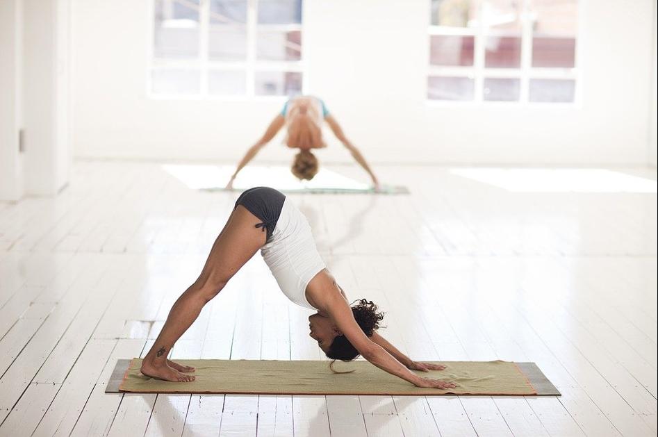 Zwei Frauen machen eine Yoga-Übung auf einer Matte in einem großen hellen Raum