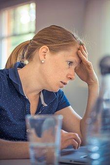 Frau hält sich den Kopf am Arbeitsplatz im Home Office